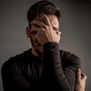calgary counselling services grieving client covering his face with his hand